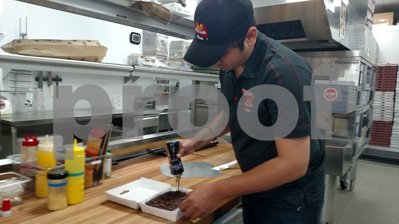 Drew Zimmerman – dzimmerman@shawmedia.com<br /> Mithilesh Gajjar, an employee at Marco's Pizza, coats a brownie with chocolate sauce for a customer. Marco's Pizza, located at 456 E. Lincoln Highway, opened its doors to the public on Aug. 21.