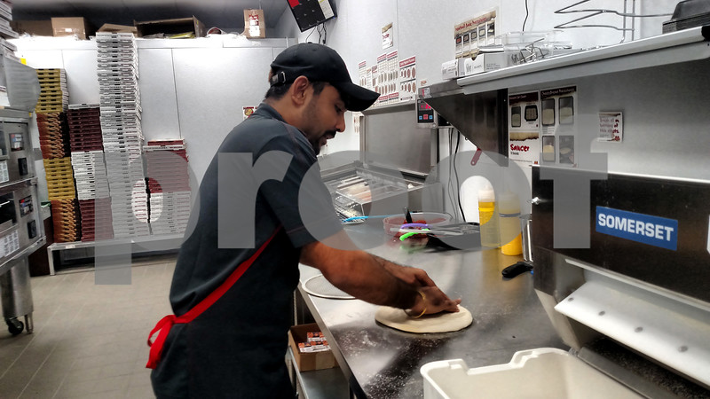 Drew Zimmerman – dzimmerman@shawmedia.com<br /> Paresh Patel, owner of Marco's Pizza on 456 E. Lincoln Highway, kneads pizza dough on Tuesday. The new restaurant opened its doors to the public on Aug. 21.