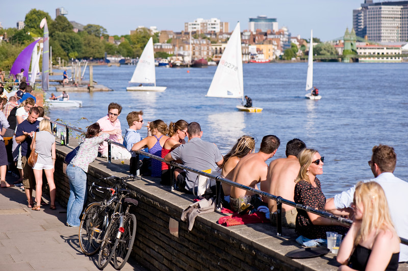 People relax on warm summer day by Thames River, Hammersmith, W6, London, United Kingdom