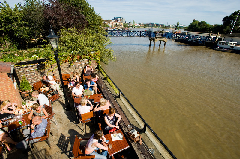 People relax in pubs ovrlooking Thames river, Hammersmith, W6, London, United Kingdom