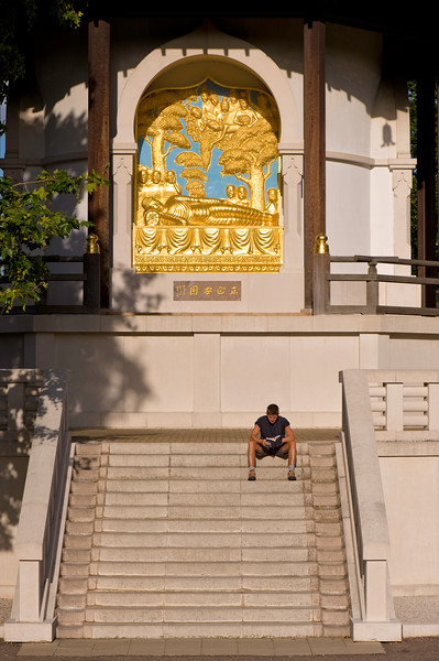 Man relaxing on steps of Buddhist Pagoda in Battersea Park, SW11, London, United KIngdom