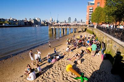 People enjoy summer afternoon by Thames River, London, United Kingdom