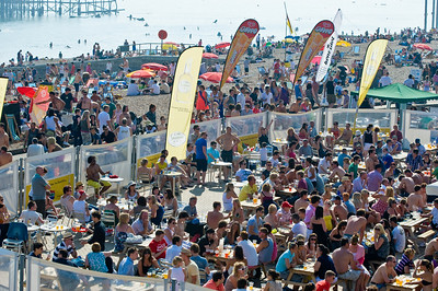 Crowded bars and pebled beach, Brighton, East Sussex, United Kingdom