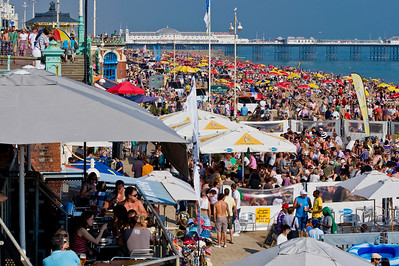 Crowded bars and pebble beach, Brighton, East Sussex, United Kingdom