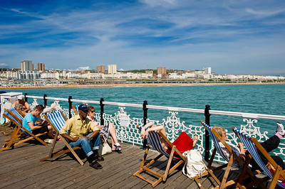 People relaxing in deck chairs on the pier, Brighton, East Sussex, United Kingdom