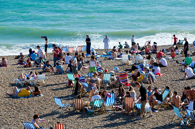 Crowded seafront and pebble beach, Brighton, East Sussex, United Kingdom