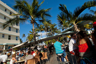 Young people  relaxing and having a drink in a bar on Ocean Drive, South Beach, Miami, USA