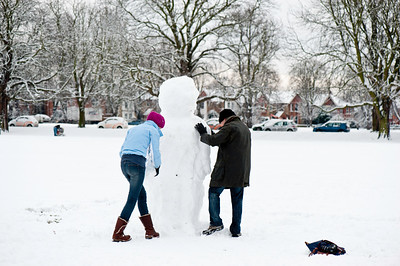 Making a snowman on The Common covered in snow, Ealing, London, United Kingdom