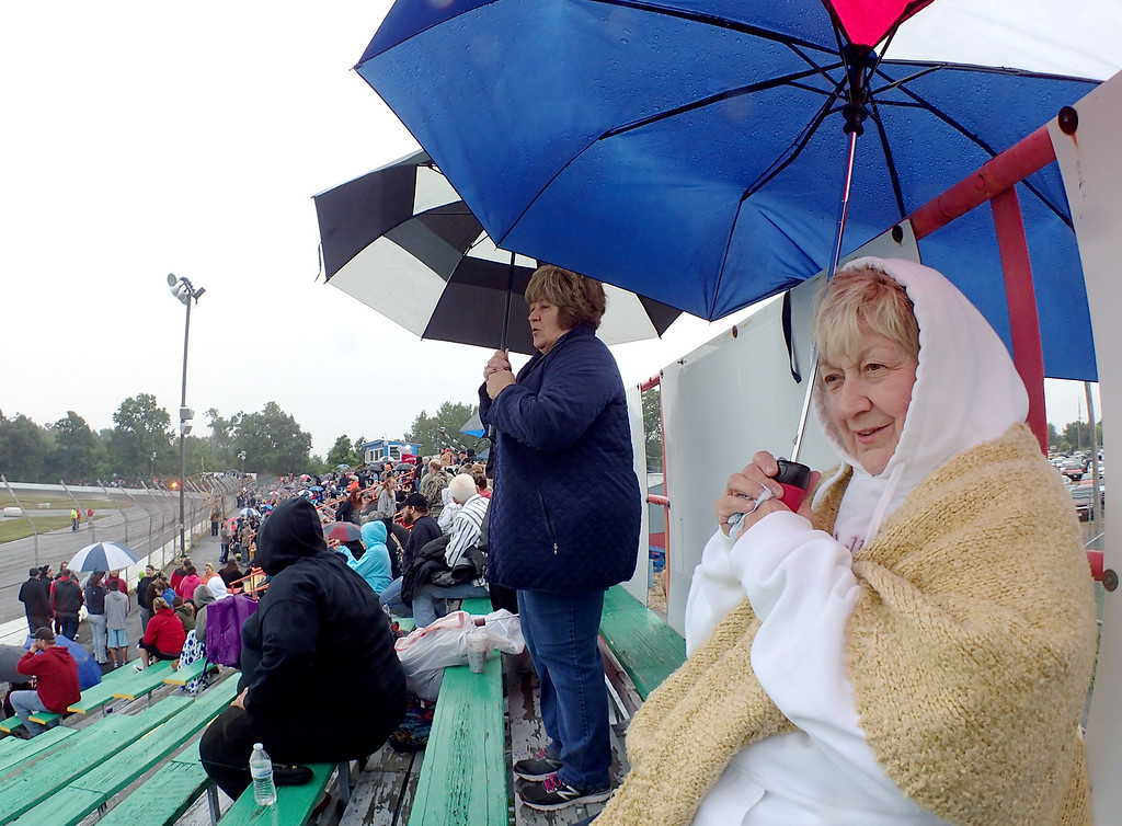 . Jonathan Tressler - The News-Herald. Mentor resident Jean Shawke, right foreground, and daughter, Painesville resident Wendy Heiss, standing in the background, both die-hard fans of The Painesville Speedway, brave the rain Sept. 2 to enjoy one of their favorite pastimes together during the venue�s grand opening under new owners.