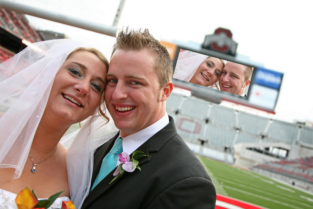 """Stacy Krupinski: Well, Erin&Tim and I planned all along to take some pictures around 'The Shoe'. The Buckeyes had an away game that Saturday. We took some shots around the stadium. We were getting some good stuff. But there was another wedding party that was ending up in all the same spots that we were in. They had 2-3 photographers, etc. But I told Erin&Tim not to worry: WE are going to get in 'The Shoe' and OUR pictures are going to be a lot better than those of that other couple. Well, after a lot of begging and pleading and sad&determined faces, the guards finally let us into the stadium. We were all so very happy with this turn of events. Now, the photo above is one from within the stadium, of course. After going through the images the idea of doing something a little different came into mind-put Erin&Tim up on the scoreboard! Those of you die-hard fans might notice that the scoreboard looks a little....BIG. Yes, the Buckeye big screen had to be enlarged quite a bit. But who is going to notice?. I haven't asked Erin&Tim about it, as it is almost 3am and the image just got finished. My point is this: I cannot promise to get all of 'my couples' into Ohio Stadium but I can promise something else. As your Wedding Day goes on, I will never quit looking for """"The Shot"""". So, if I pull you aside and say, 'Hey, let me get 5 minutes with you two"""", please come with me. <br />    Anyway, it's now about 3:30(I type SLOWLY) and I've gone on quite long enough. If you've made it this far, I thank you!"""