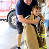 Jonathan Tressler — The News-Herald <br> Mike Toman, a Mentor Fire Department firefighter/paramedic helps 6-year-old Matteo Carini, who was born with Down syndrome and battles Crohn's and and liver disease, try on a turnout coat at Fire Station No. 5 Sept. 1 during a surprise party for Matteo, who has an affinity for all things fire service.