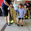 Jonathan Tressler — The News-Herald <br> Matteo Carini, 6, forground, gets ready to try on a turnout coat as his little brother, Luca, 4, does the sae in the background during a surprise birthday party for Matteo at Mentor Fire Station No. 5 Sept. 1.