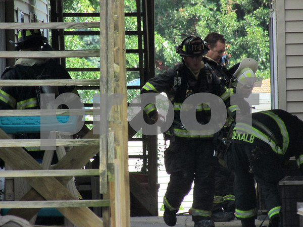 DeKalb firefighters organize outside an apartment that caught fire Friday morning at Canterbury Place Apartments on 615 Meadow Creek Drive. No injuries were reported, and the fire was isolated to a single unit in the building, officials said.