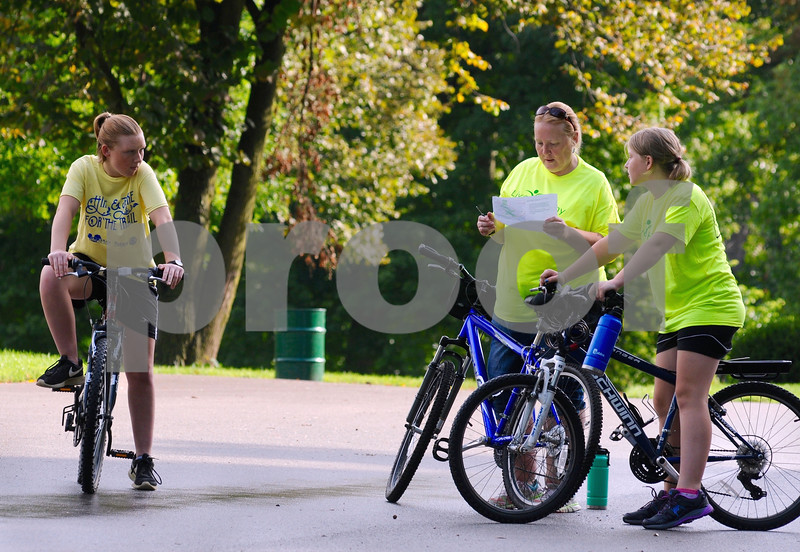 Jeannine Szostak and daughters Cailey (right), 11, and Carrie, 14, check out the route for the Hike and Bike for the Trail event on Monday at Hopkins Park in DeKalb.  Steve Bittinger - For Shaw Media