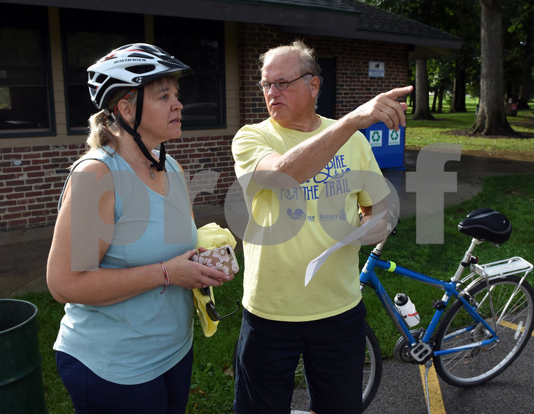 Tammy Sutphin and DeKalb Rotary Club volunteer John Horn discuss the route for the Hike and Bike for the trail event held Monday at Hopkins Park.  Steve Bittinger - For Shaw Media