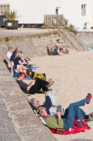 People reading and relaxing on the beach, St Ives, Cornwall, United Kingdom