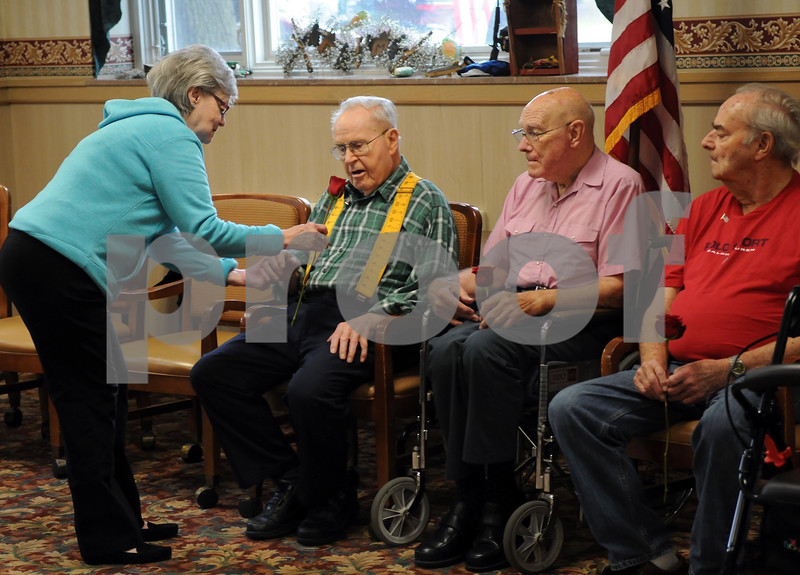 Barb City Manor resident Sally Barkey presents roses to resident veterans Gene Bristow (from left), Warren Lowe, and Ralph Phillips on Saturday during a stop on the 11th Annual Veterans Weekend Motorcycle Motorcade.  Steve Bittinger - For Shaw Media
