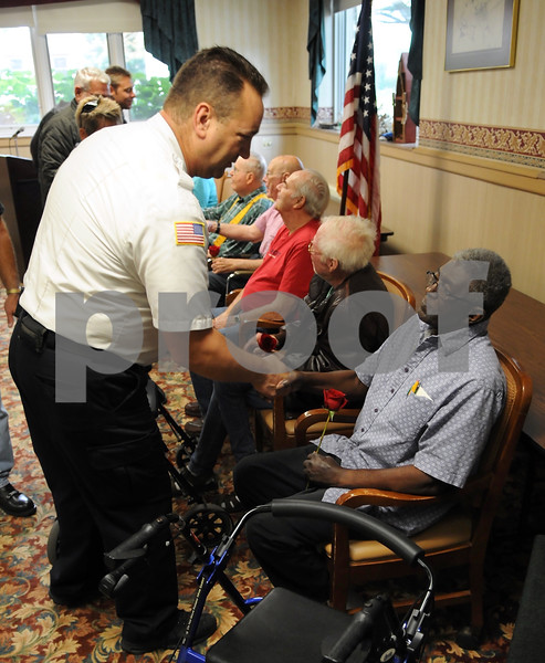 DeKalb Deputy Fire Chief James Zarek thanks Vietnam veteran Bob Phifer for his service, during a ceremony honoring veterans at Barb City Manor on Saturday.  Steve Bittinger - For Shaw Media