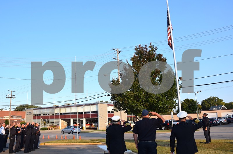 Katrina J.E. Milton - kmilton@shawmedia.com<br /> Members of the Sycamore Fire Department salute as the American flag is lowered to half-staff during the 9/11 Memorial Service held Monday by the Sycamore Fire and Police Department.