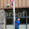 Sam Buckner for Shaw Media.<br /> Steve Hayes lowers the flag to half mast during the 9/11 remembrance day assembly on Monday September 11, 2017.