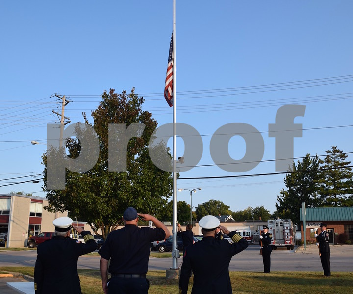 Katrina J.E. Milton - kmilton@shawmedia.com<br /> Members of the Sycamore Fire Department salute as Sycamore firefighter and paramedic Bill Reynolds lowers the American flag to half-staff during the 9/11 Memorial Service held Monday by the Sycamore Fire and Police Department.