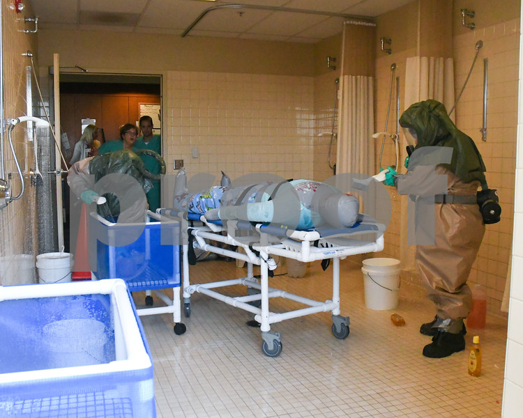 Members in hazard material suits help shower off patients who may not be able to shower them self after being expose to a hazards material with soap and water during a hazard material simulation Sep. 12 at Kishwaukee Hospital.
