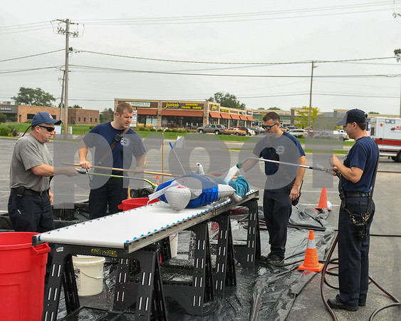 Bob Maciejewski, Travis Karr, Greg Thorton and Chris Krupa, Left to right, rinse off dummies with soap and water as part of a hazard material simulation exercise held at Kishwaukee Hospital on Sep. 12th.