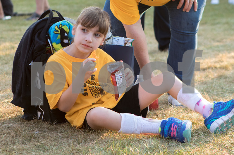 Sam Buckner for Shaw Media.<br /> Abbey Ross, 9, sits in the grass and eats a bag of chips before the game on Friday September 15, 2017.