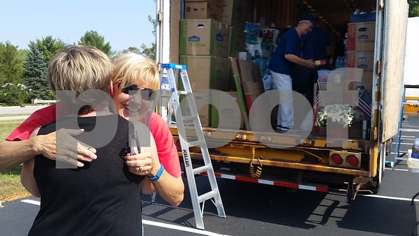 Christopher Heimerman – cheimerman@shawmedia.com<br /> Kathy Elliott (far left) of DeKalb hugs Crossview Church member and volunteer Kathy Hall of Genoa after donating goods for hurricane relief in Texas, while Hall's nephew, 26-year-old Justin Campbell, helps organize the truck Friday afternoon in the church parking lot.