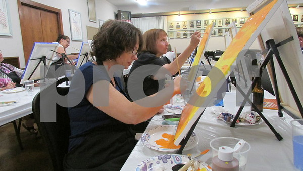 Aimee Barrows for Shaw Media<br /> Sherry Christensen of Sycamore works on her painting during a fundraiser for needy DeKalb County veterans Saturday night at the Sycamore VFW.