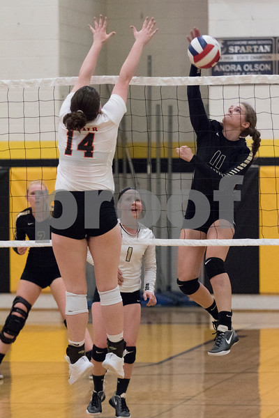 Sam Buckner for Shaw Media.<br /> Sycamore's Faith Reynolds spikes the ball while Emma Fellabaum of Dekalb tries to block the ball on Wednesday September 20, 2017.