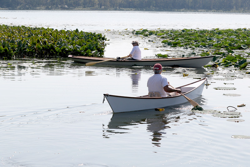Jonathan Tressler — The News-Herald <br> Cleveland Amateur Boatbuilding and Boating Society President Ed Neal, paddling in the group's Six-Hour Canoe prototype, follows wife, Susan Lewis, who is piloting an 18-foot, sliding-seat performance rowing boat called a Firefly, out into Bass Lake in Munson Township.
