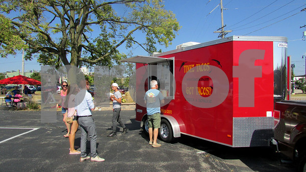 Folks gather around Tinez Tacos food truck during Trucktober Fest on Sunday at Faranda's in DeKalb.