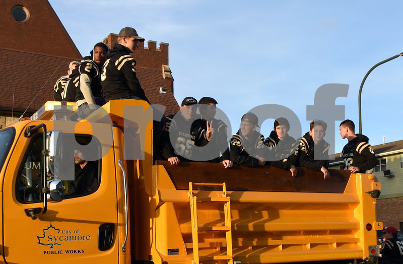 Sycamore High School football players ride in the homecoming parade on Wednesday.<br /> Steve Bittinger - For Shaw Media