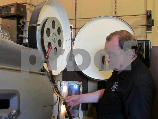 Stanley Hightower, a former business partner of the Music Box Theatre in Chicago, inspects film inside of a 35mm projector Sunday.The projector is one of two being restored to show old films at the Egyptian Theatre in downtown DeKalb.