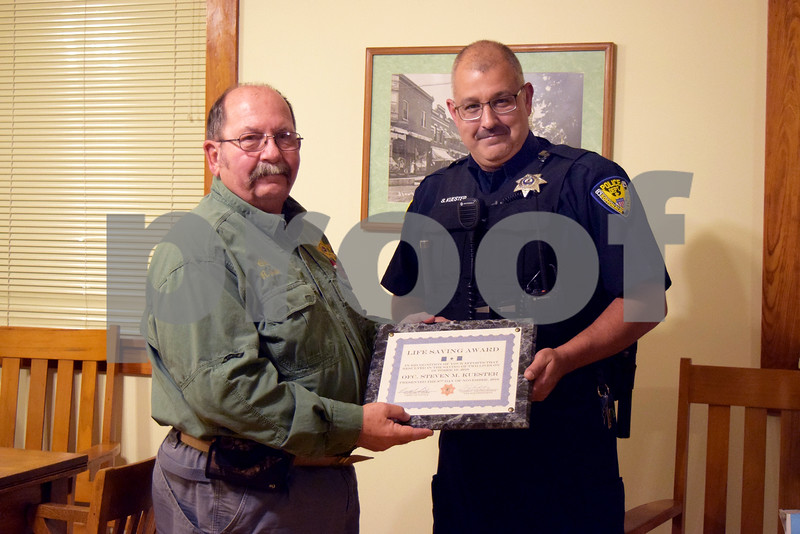 Somonauk Police Chief Rich Smith (left) awarded officer Steve Kuester the Somonauk Police Department's Life Saving Award during the Nov. 9, 2016, Somonauk Village Board meeting. During the late hours of Oct. 18, 2016, Kuester noticed smoke and alerted the fire department. After locating the fire, he woke up the family, Janise and Cager Collins, and helped them to safety.