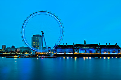 London Eye by County Hall Building overlooking Thames River at night, London, United Kingdom