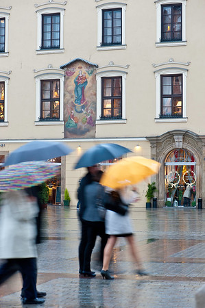People walking in the rainy Main Square, Cracow, Poland