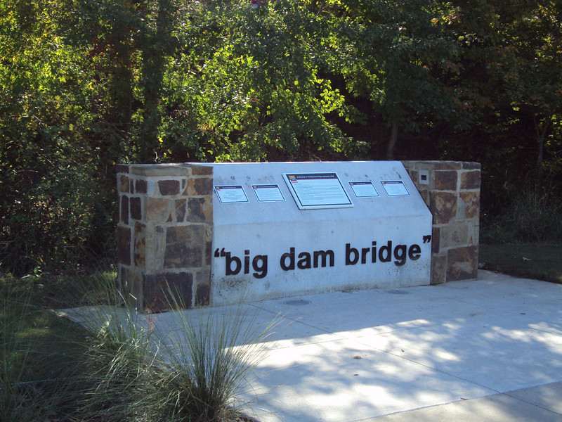 """The <a href=""""http://www.bigdambridge.com/"""">Big Dam Bridge</a> in Pulaski County, Arkansas connects Rebsamen Park in Little Rock with Cooks Landing Park in North Little Rock. This extraordinary piece of infrastructure is nearly one mile in length and was constructed by drilling into the top of the Murray Lock and Dam on the Arkansas River. The bridge is an integral portion of the Millennium Trail, a collection of riverside trails along both sides of the Arkansas River that, when completed, will create a 15-mile multi-use bike path. The bridge's exemplary design elements, which include L.E.D. lighting and generous 14-foot right-of-way, have resulted in twelve awards from a number of professional associations and societies. The bridge opened September 30, 2006.  Federal TE funding amounting to $300,000 was awarded to the project leveraging a local match of over $11 million."""