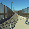 "Tall fencing lines the bridge allowing children to play freely. A dashed white line manages traffic in both directions.  The <a href=""http://www.bigdambridge.com/"">Big Dam Bridge</a> in Pulaski County, Arkansas connects Rebsamen Park in Little Rock with Cooks Landing Park in North Little Rock. This extraordinary piece of infrastructure is nearly one mile in length and was constructed by drilling into the top of the Murray Lock and Dam on the Arkansas River. The bridge is an integral portion of the Millennium Trail, a collection of riverside trails along both sides of the Arkansas River that, when completed, will create a 15-mile multi-use bike path. The bridge's exemplary design elements, which include L.E.D. lighting and generous 14-foot right-of-way, have resulted in twelve awards from a number of professional associations and societies. The bridge opened September 30, 2006.  Federal TE funding amounting to $300,000 was awarded to the project leveraging a local match of over $11 million."