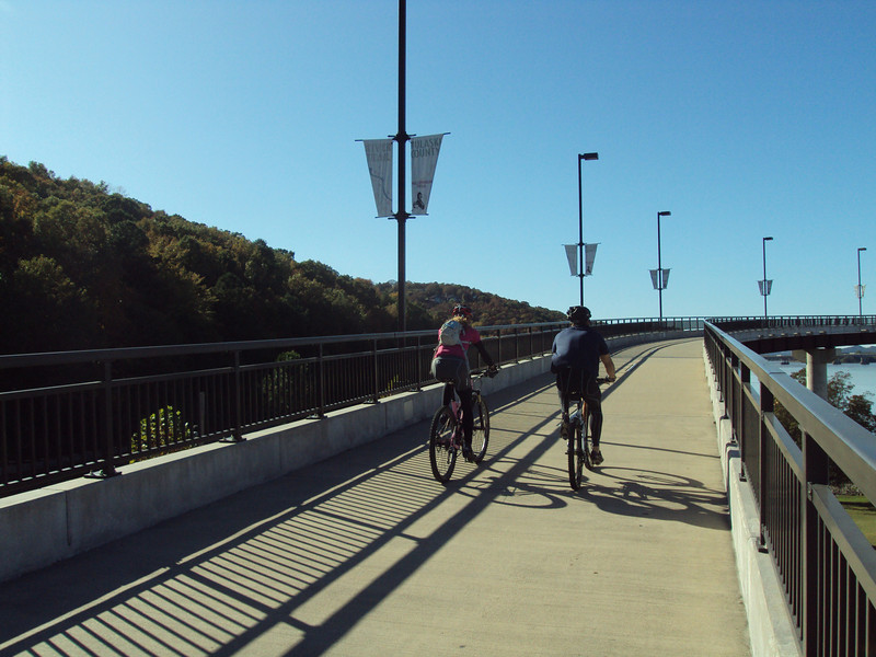 "The <a href=""http://www.bigdambridge.com/"">Big Dam Bridge</a> in Pulaski County, Arkansas connects Rebsamen Park in Little Rock with Cooks Landing Park in North Little Rock. This extraordinary piece of infrastructure is nearly one mile in length and was constructed by drilling into the top of the Murray Lock and Dam on the Arkansas River. The bridge is an integral portion of the Millennium Trail, a collection of riverside trails along both sides of the Arkansas River that, when completed, will create a 15-mile multi-use bike path. The bridge's exemplary design elements, which include L.E.D. lighting and generous 14-foot right-of-way, have resulted in twelve awards from a number of professional associations and societies. The bridge opened September 30, 2006.  Federal TE funding amounting to $300,000 was awarded to the project leveraging a local match of over $11 million."