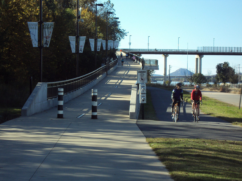 "Though the bridge's approach is long, the ramp's 5% grade is easily navigated by a variety of users.   The <a href=""http://www.bigdambridge.com/"">Big Dam Bridge</a> in Pulaski County, Arkansas connects Rebsamen Park in Little Rock with Cooks Landing Park in North Little Rock. This extraordinary piece of infrastructure is nearly one mile in length and was constructed by drilling into the top of the Murray Lock and Dam on the Arkansas River. The bridge is an integral portion of the Millennium Trail, a collection of riverside trails along both sides of the Arkansas River that, when completed, will create a 15-mile multi-use bike path. The bridge's exemplary design elements, which include L.E.D. lighting and generous 14-foot right-of-way, have resulted in twelve awards from a number of professional associations and societies. The bridge opened September 30, 2006.  Federal TE funding amounting to $300,000 was awarded to the project leveraging a local match of over $11 million."