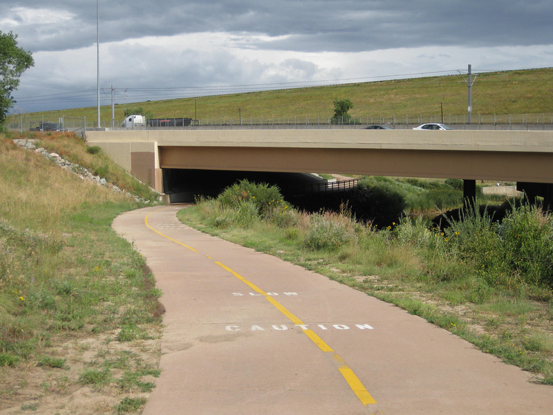 The trail passes under I-25.<br /> <br /> The Cherry Creek Trail runs from downtown Denver for more than 40 miles, connecting multiple suburbs and counties to the heart of the city.  The trail is below grade for much of the way, following the bed of the creek.  This minimizes the number of road crossings, and thus reduces conflicts between cars and nonmotorized travelers.  Residences, jobs, schools, parks, and shopping are all seamlessly connected on the trail corridor.<br /> <br /> The trail is a regional effort.  Various TE grants with differing sources of matching funds have contributed to constructing and improving the trail including $417,000 in 1999 to the City of Denver, $164,844 in 2001 to the town of Glendale, $365,000 in 2003 to Arapahoe County, and an additional $315,000 to Denver in 2005.  The end product is a trail that is one of the spines of a regional network of trails connecting travelers and destinations throughout the Denver area.