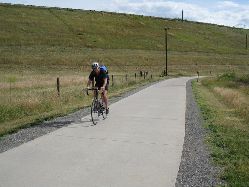 A rider on the Cherry Creek Dam Trail.<br /> <br /> The Cherry Creek Trail runs from downtown Denver for more than 40 miles, connecting multiple suburbs and counties to the heart of the city.  The trail is below grade for much of the way, following the bed of the creek.  This minimizes the number of road crossings, and thus reduces conflicts between cars and nonmotorized travelers.  Residences, jobs, schools, parks, and shopping are all seamlessly connected on the trail corridor.<br /> <br /> The trail is a regional effort.  Various TE grants with differing sources of matching funds have contributed to constructing and improving the trail including $417,000 in 1999 to the City of Denver, $164,844 in 2001 to the town of Glendale, $365,000 in 2003 to Arapahoe County, and an additional $315,000 to Denver in 2005.  The end product is a trail that is one of the spines of a regional network of trails connecting travelers and destinations throughout the Denver area.