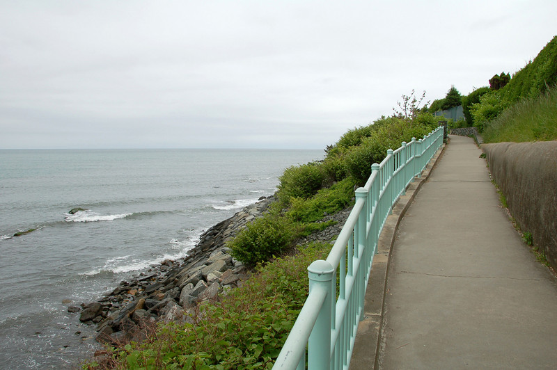 "The 3.5-mile Cliff Walk is considered one of Newport, Rhode Island's top attractions. The scenic walkway, which runs from First Beach to Bailey's Beach, is bordered by the Rhode Island Sound and Atlantic Ocean on one side, and many of the famous seaside Newport Mansions on the other. In 1975, the Cliff Walk was designated as a National Recreation Trail. <br /> <br /> Local historians believe that the first paths along the Cliff Walk shore line were forged by deer, then by the Narragansett Indians, and later by colonial setters. Public use of the Cliff Walk was protected under the ""Fisherman's Rights"" clause in the Colonial Charter of King Charles II, and later in the Rhode Island Constitution which grants the public the ""privileges of the shore.""<br /> <br /> Efforts to establish the Cliff Walk began in about 1880, when a number of owners of adjacent property joined together to make improvements. Over time the property owners and the public made improvements to the path piece by piece. Portions of the Cliff Walk were badly damaged by hurricanes in 1938 and 1954. Between 1970 and 1976, the U.S Army Corps of Engineers made basic repairs to the path. <br /> <br /> Improvements continued in the early 1980s, and in 1994 TE funds were awarded (under Category 1) for further restoration that included new retaining walls to prevent erosion along the cliffs and repairs to areas damaged by Hurricane Bob in 1991. Federal Award: $1,200,000; Local Match: $300,000; Total: $1,500,000<br /> <br /> For more information on the Cliff Walk visit  <a href=""http://www.cliffwalk.com/"">http://www.cliffwalk.com/</a>"