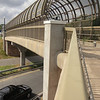 The Forest Glen Pedestrian Bridge provides a safe and accessible way to travel along Georgia Avenue and to cross the Capital Beltway I-495. I-495 crosses Georgia Avenue between Wheaton and Silver Spring very close to the Forest Glen Metro station. This intersection was very dangerous and on one side had 5 at grade crossings. <br /> <br /> The high frequency of commuters and locals who rely upon the Metro station and Georgia Avenue as a means of transportation was a major reason to construct the bridge. Furthermore the neighborhoods south of I-495 were cut off from the surrounding area by these unsafe crossings. Funding for the bridge was approved in 2000 and $2.878 million came from TE funding and another $2.878 million from local match sponsors. The project included the bridge which eliminated at grade crossing.  The bridge crosses over two highway entrance ramps, two exit ramps, and goes underneath the beltway itself.<br /> <br /> This project is another link in Montgomery County's continued efforts to build bicycle and pedestrian bridges at and around major regional highways including I-270 andI-495. Without TE funding, these crossing would continue to place commuters, walkers, and bikers in harm's way.