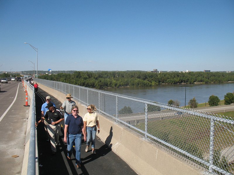 The Heart of America Bridge became the first bridge in the Kansas City region to offer a safe, barrier-separated, and efficient way to cross the Missouri River on bicycle or foot. The shoulder of the northbound side of the bridge was retrofitted to include a mile long two-way path which runs from E. 3rd Street to 10th Avenue. <br /> <br /> When the Missouri Department of Transportation conducted a bike/pedestrian feasibility study as part of the I-29/35 environmental impact statement, the Heart of America Bridge was identified as an alternative route to move bicyclists across the river. The path officially opened in October of 2010, two years earlier than planned thanks to the availability of American Recovery and Reinvestment Act funding. The category 1 project used $2.42 million in Transportation Enhancements funding to complete the project.