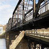 """<a href=""""http://www.flickr.com/photos/kordite/2075220200/sizes/o/in/photostream/"""">Photo Credit</a>  The Hot Metal Bridge in Pittsburgh, Pennsylvania was originally built in the 1880s to transport hot steel across the Monongahela River to rolling mills on the other side. This significantly improved business as steel previously had to be reheated. A century later and the bridge is now providing passage over the Monongahela River for bicyclists and pedestrians. A TE fund of over $6,500,000 was matched locally by $730,000 and went towards the removal of lead-based paint, to build a bridge over Second Ave., and to connect the bridge to the Eliza Furnace trail. The bridge reopened in November of 2007 and is a vital connection to the Pittsburgh bicycle network."""