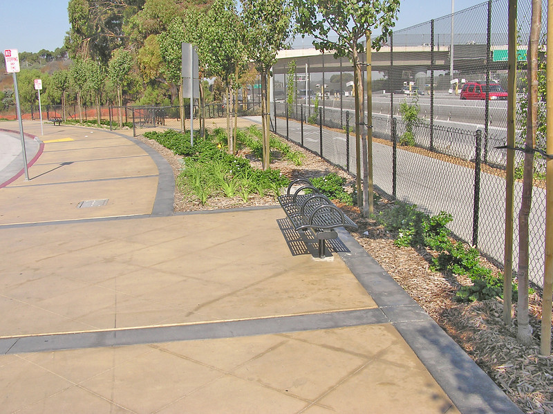 A portion of the new plaza and bicycle route.  New trees, once mature, will provide shade for travelers at the crossing.<br /> <br /> The US/Mexico border between San Diego, CA and Tijuana in Mexico is the busiest land border crossing in the world.  Over 30 million vehicles and 18 million pedestrians cross annually, with the border gateway at Interstate 5 suffering significant congestion. Additional delays and safety issues were caused by large numbers of nonmotorized travelers coming into conflict with cars and trucks at the crossing.<br /> <br /> The California Department of Transportation initiated the International Friendship Plaza project to address these issues, and to transform the crossing at Interstate 5 from one more large piece of ugly infrastructure to a human-scale, comfortable, interesting, and clean border crossing experience. The project created a new plaza and promenade on the California side of the crossing, improved circulation through transit and private-vehicle drop-off areas, accessible pathways and turnstiles for disabled travelers, bicycle parking facilities, and formal pedestrian street crossing routes. Public art, historic interpretation, trash receptacles, lighting, and plantings all enhance the experience for travelers passing through the crossing.<br /> <br /> The project was funded in part through $2,246,000 in federal TE funds in 2003. In 2008, the completed project was recognized as outstanding with an Exemplary Human Environment Initiatives (EHEI) award by the Federal Highway Administration.