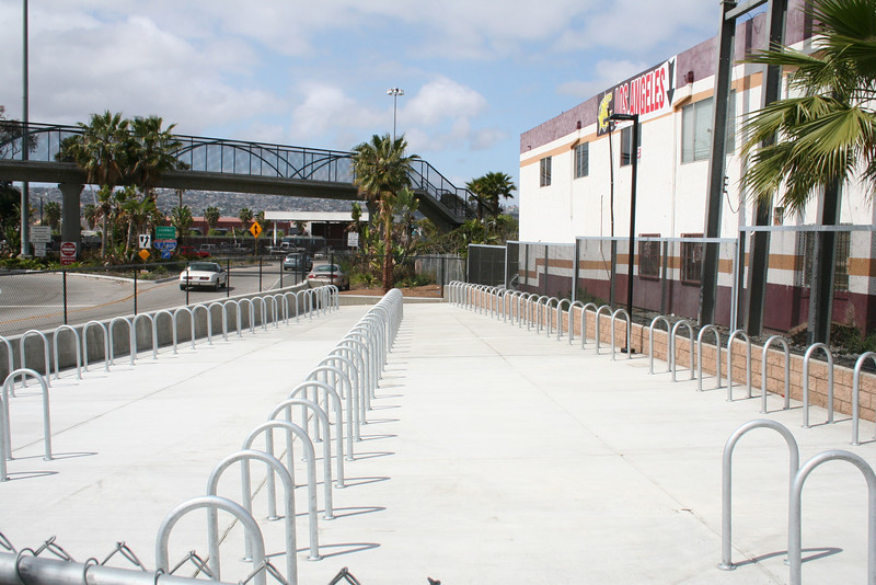 A new bicycle parking facility was installed on the northeast side of Interstate 5, near the San Diego Trolley station.<br /> <br /> The US/Mexico border between San Diego, CA and Tijuana in Mexico is the busiest land border crossing in the world.  Over 30 million vehicles and 18 million pedestrians cross annually, with the border gateway at Interstate 5 suffering significant congestion. Additional delays and safety issues were caused by large numbers of nonmotorized travelers coming into conflict with cars and trucks at the crossing.<br /> <br /> The California Department of Transportation initiated the International Friendship Plaza project to address these issues, and to transform the crossing at Interstate 5 from one more large piece of ugly infrastructure to a human-scale, comfortable, interesting, and clean border crossing experience. The project created a new plaza and promenade on the California side of the crossing, improved circulation through transit and private-vehicle drop-off areas, accessible pathways and turnstiles for disabled travelers, bicycle parking facilities, and formal pedestrian street crossing routes. Public art, historic interpretation, trash receptacles, lighting, and plantings all enhance the experience for travelers passing through the crossing.<br /> <br /> The project was funded in part through $2,246,000 in federal TE funds in 2003. In 2008, the completed project was recognized as outstanding with an Exemplary Human Environment Initiatives (EHEI) award by the Federal Highway Administration.